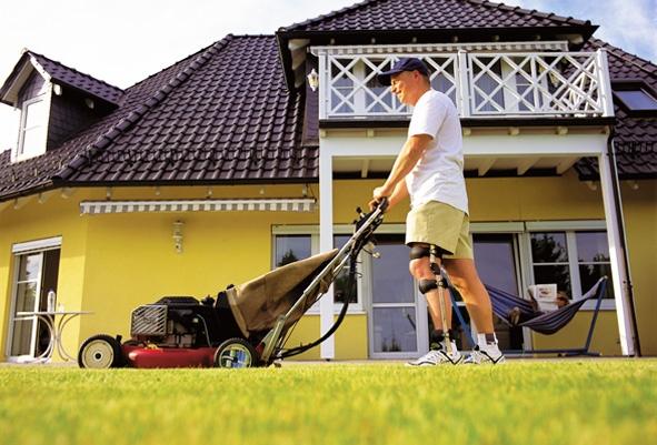 man leg orthotics mowing lawn
