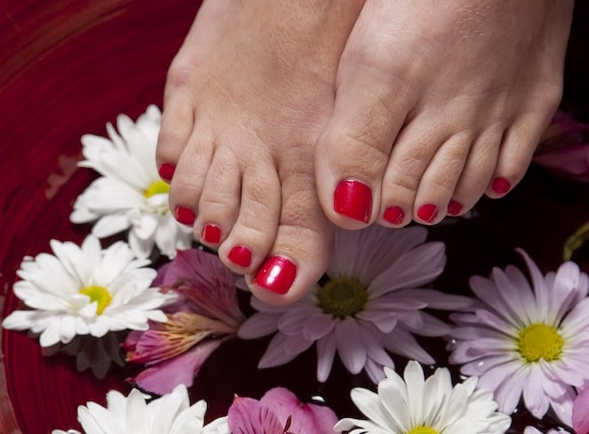 feet over bowl of water with flowers